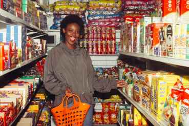 funny black woman choosing food in grocery shop