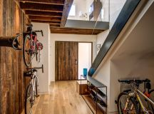 contemporary entry hall idea hanging bikes standing bike under staircase hall shoes rack medium toned wood floors raw rustic wood walls raw rusic entrance door
