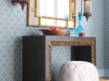 eclectic dressing table in black accented with gilt carvings bamboo paneled mirror hidehair ottoman chair in white Moroccan style sconces