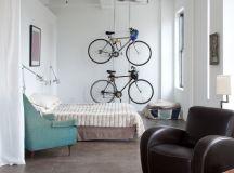 industrial bedroom idea a couple of hanging bike racks turquoise corner chair dark brown leather armchair cowhide area rug white walls