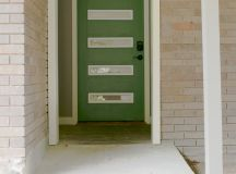 mid century front door idea in green accented with narrow glass windows red bricks exterior walls concret floors