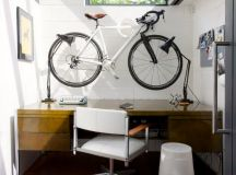 modern home office idea ornamental mounted wall bike hardwood working table modern working chair with wheels white ceramic walls terracotta tiles floors