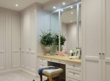 traditional walk in closet with recessed makeup vanity table accented with wood top wood base vanity bench