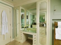 walk in closet with recessed glass top makeup vanity frameless mirror