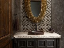dark vintage vanity idea white countertop black painted wood cabinets gold toned & textured mirror's frame small mosaic tiles wall background