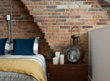 loft bedroom idea red bricks walls modern bed frame with wood headboard light toned wood floors traditional table lamp a cluster of candles