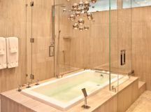 modern bathroom idea white bathtub with oak frames walk in shower with clear glass door gold toned galaxy light fixture idea