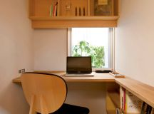 small clean line home office L shaped wood working desk floating wood shelves side wood shelves black leather working chair with wood frames wood floors