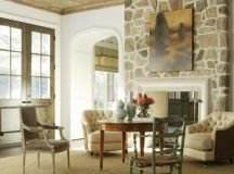 traditional family room idea fireplace with stone surrounds vintage style tufted armchairs shabby wood chairs juted carpet exposed wood ceilings