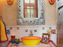 vintage style bathroom vanity with pop colors touch tiles countertop & backsplash with hand crafted tiles mirror with hand crafted metal frame tuscan style vanity lamps yellow vessel sink red cabinets