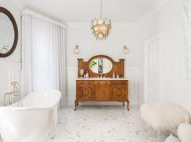 victorian style bathroom idea medium toned wood bathroom vanity with marble countertop round mirror white tiles floors white bathtub white window curtains