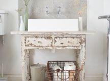 vintage bathroom vanity farmhouse sink a couple of faucets leaf patterned tiles floors grey tiles backsplash a couple wall sconces