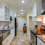 Beautiful kitchen with solid surface counter tops and stainless range hood.