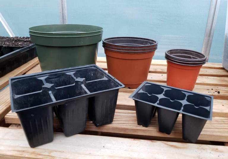 Different types and sizes of reusable containers that can be used to start seeds, including small pots and six packs.