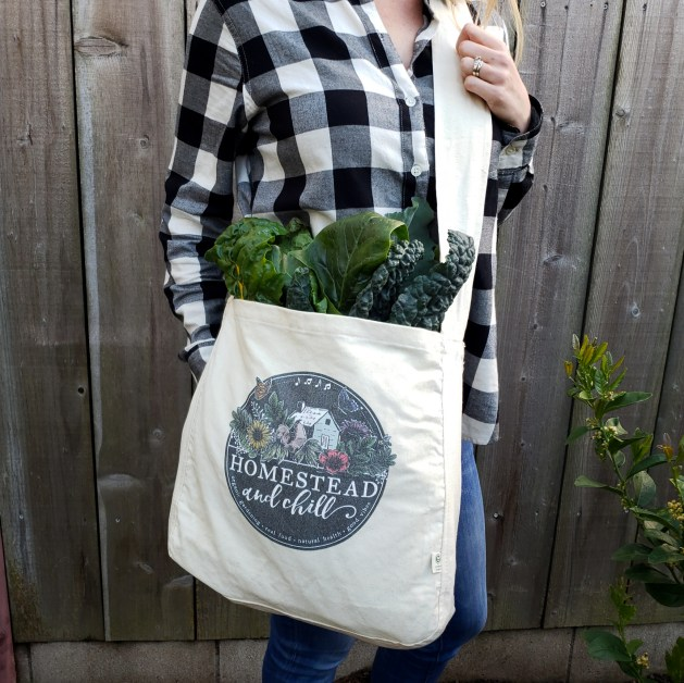 A Homestead and Chill canvas market bag  is shown. The circular logo is on the center of the bag and there are vegetable greens poking up out of the top of the bag which is slung over a persons shoulder.