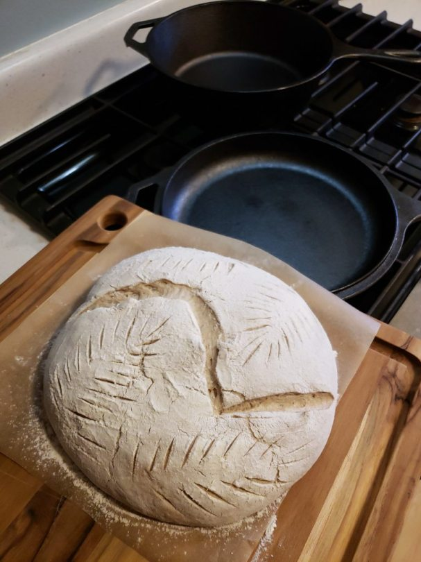 A loaf of uncooked sourdough, sitting on a cutting board. It is poised near a cast iron pan, ready to carefully be slid into it, and then into the oven.