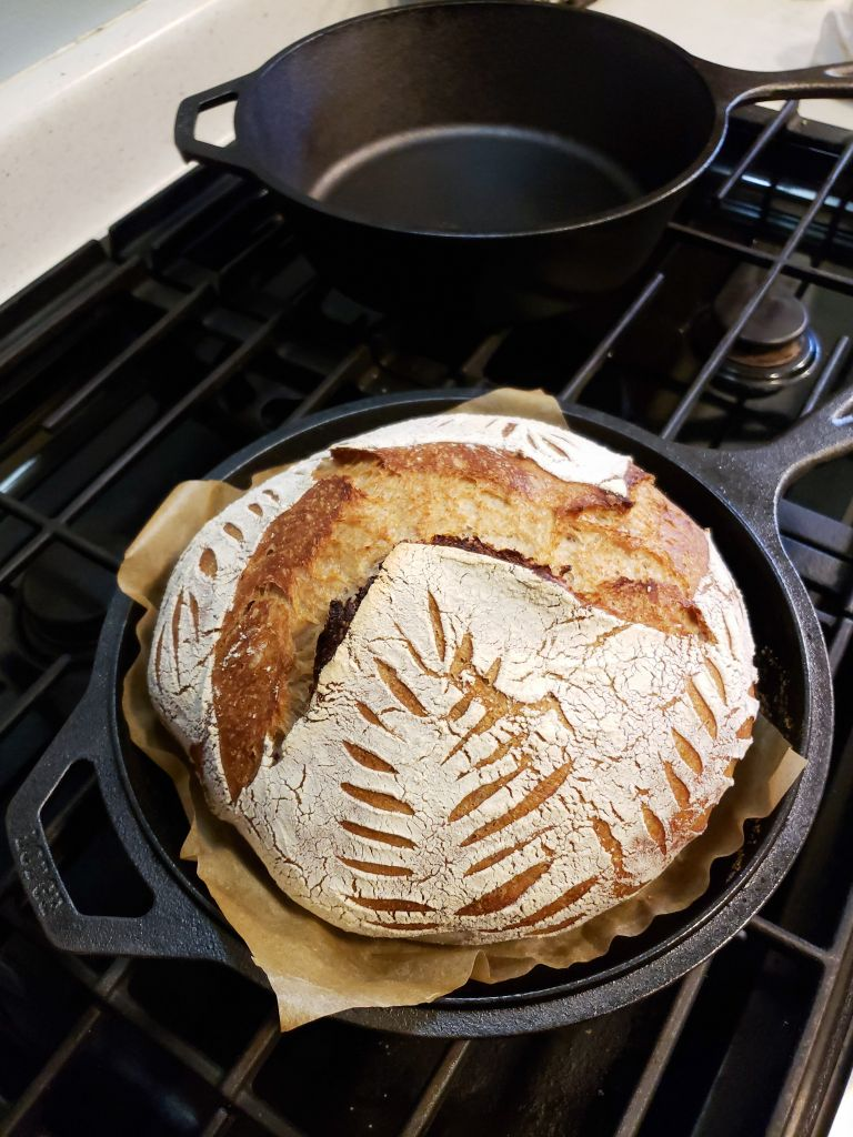 The now baked sourdough loaf, fresh out of the oven. It is sitting on top of the stove, still in the cast iron pan called a combo cooker. The pretty leaf design turned out nicely around the sides.