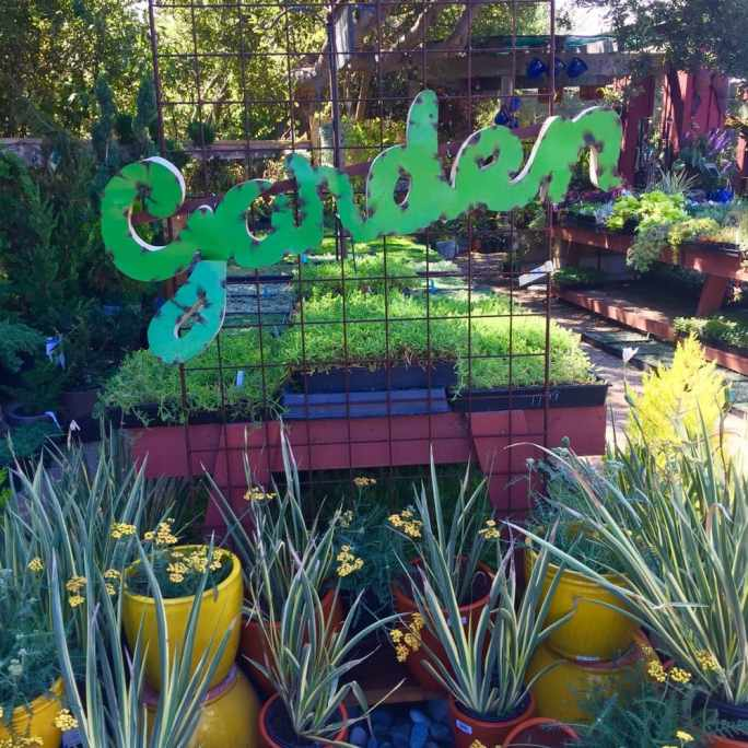"""One side of a rusted metal arch is shown with a metal sign attached across it with the word """"garden"""" in green cursive. There are various grasses or agaves in pots below the sign. Beyond are display tables with many herbs and perennials in smaller flats."""