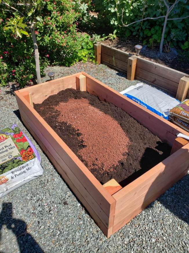 An image of a newly built redwood raised bed, only about half full at this time. In the bed, there is a combination of soil and compost, with some red volcanic rock on top, about to be mixed and then continued to be filled.