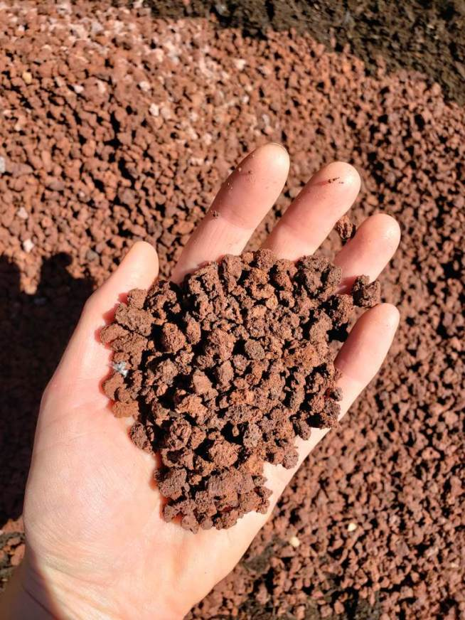 A hand holding small red lava rock pieces, that are being added to the new raised bed.