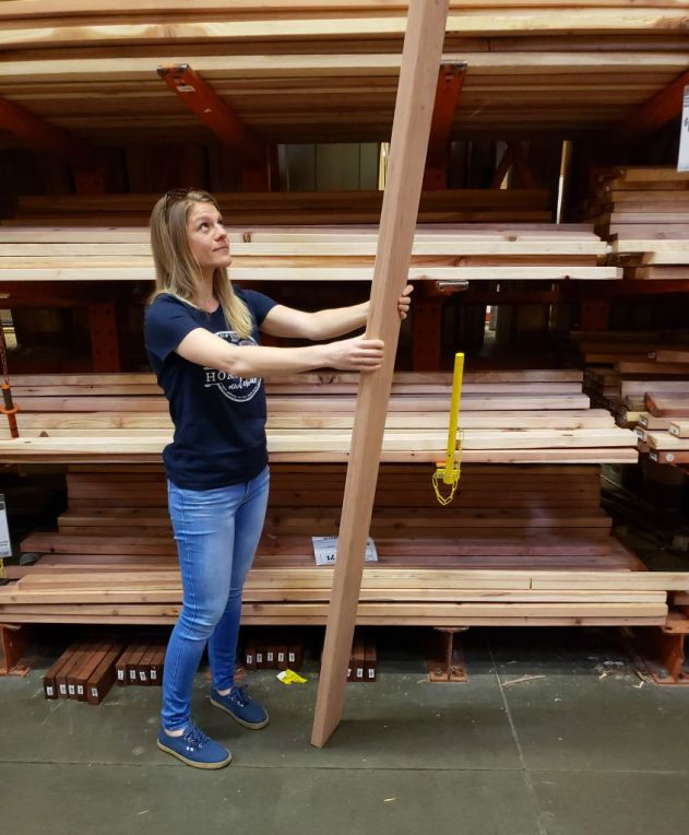 A photo of DeannaCat at home depot in the lumber section. She is a blonde woman with slender build, wearing blue jeans and a blue shirt, holding up a long redwood board vertically, peering up at it, standing in front of racks of boards.