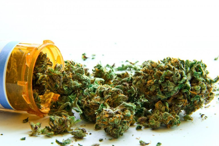 A stock image of a prescription bill bottle dumped on its side, with nugs of marijuana spilling out instead of pills.