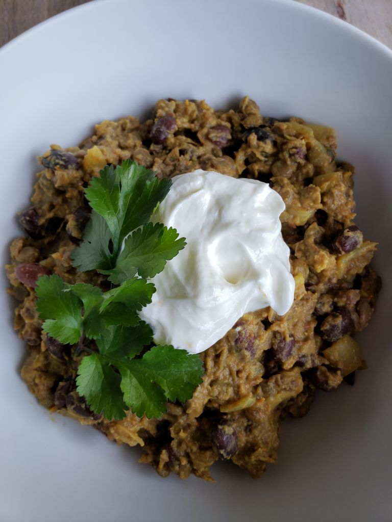A white bowl full of cooked curry lentils. A dollop of plain yogurt is on top, along with a sprig of cilantro.