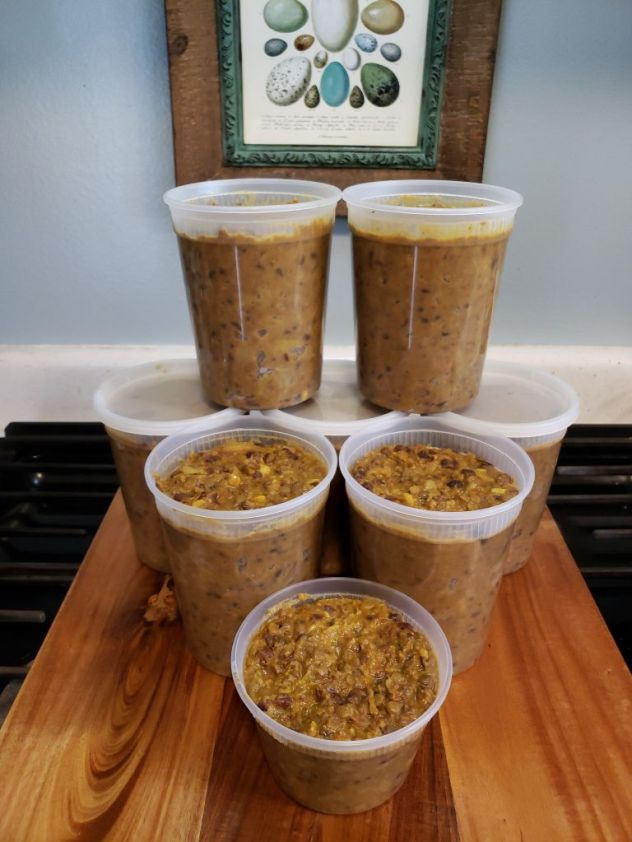 Shown are 8 quart size plastic freezer containers, full of finished curry lentils and stacked in a pyramid.