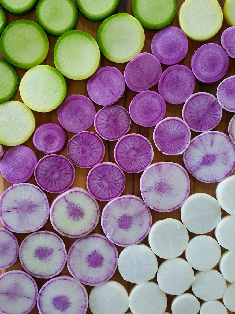 An image of colorful cut radishes, in slices laid out side by side on a cutting board, looking down. They're organized by color, going from white to purple to green.