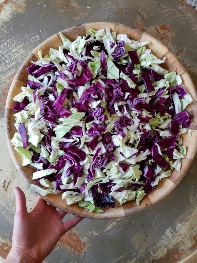 A large wooden bowl of green and red chopped cabbage.