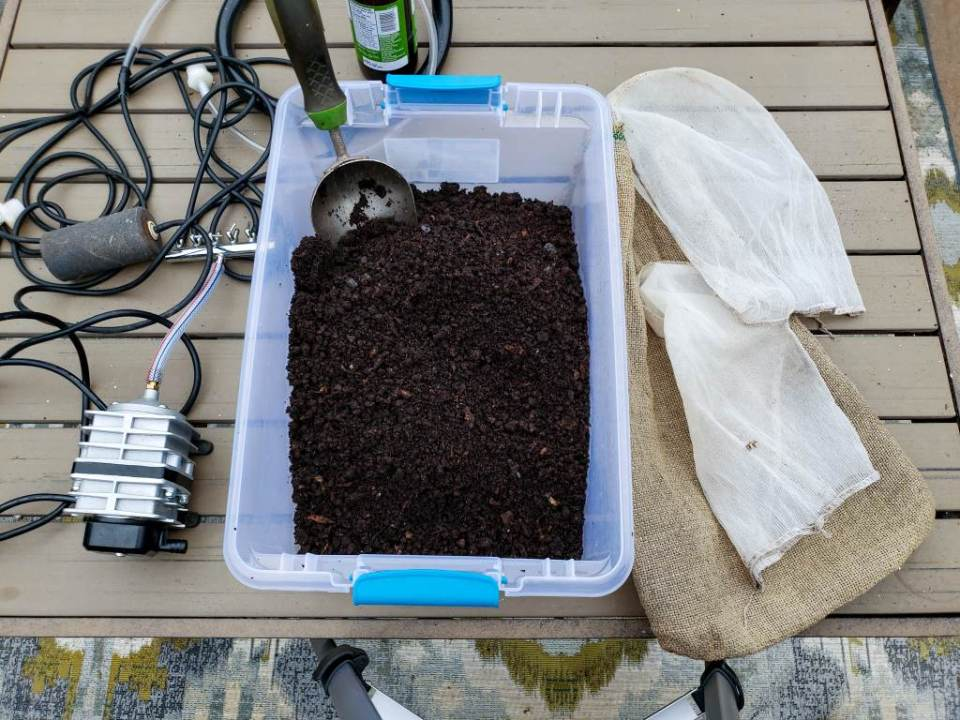 A small plastic tote of freshly harvested worm castings sit on a table next to mesh paint strainer bags, and an air pump - some of the supplies used in brewing compost tea.