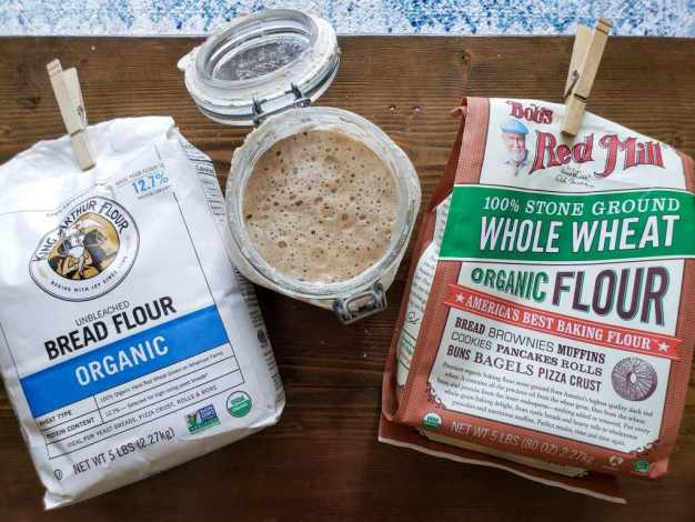 An image looking down on two bags of flour on a dark brown wood table, with a glass jar of bubbly sourdough starter in the middle. One bag reads Unbleached Organic Bread Flour by King Arthur Flour, and the other is 100% Stone Ground Whole Wheat Organic Flour from Bob's Red Mill.