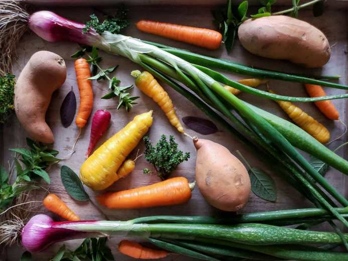 Looking down on some of the fresh ingredients used in this recipe, artfully laid out on a cutting board in moody lighting. There are several sweet potatoes, carrots, red onions with their greens still attached, and a variety of fresh herbs on display.