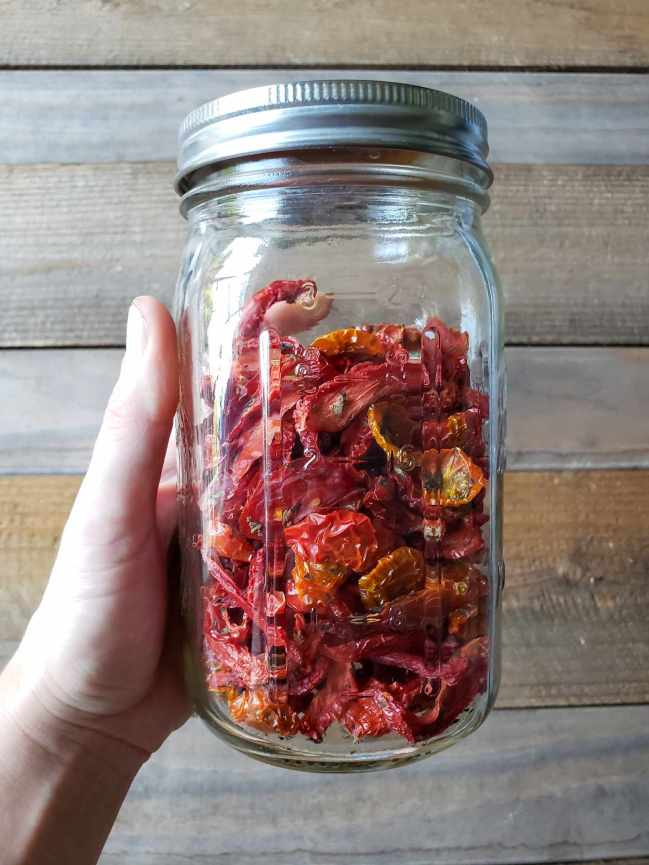 A hand holds a quart mason jar full of sun dried tomatoes in front of a barn wood backdrop.