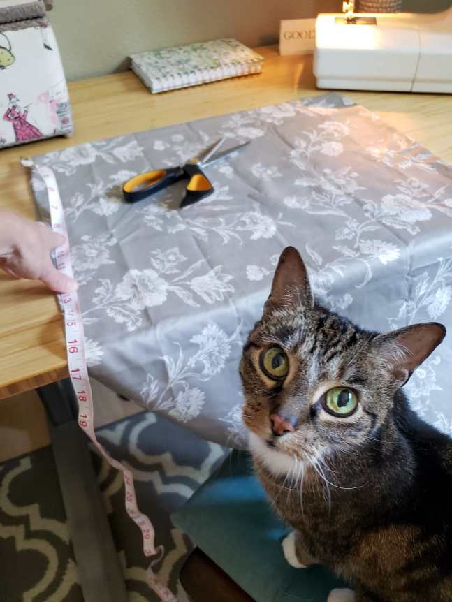 A pillow case is laid out on a light wood/bamboo table with the end of the case hanging just off of the edge of the table. A grey/brown tabby cat is in the immediate foreground staring directly at the camera. There is a hand holding a fabric tape measure on the pillow case while there is a pair of scissors sitting on the fabric case. On the back of the table there is the lower half of a sewing machine shown as well as part of a sewing basket.