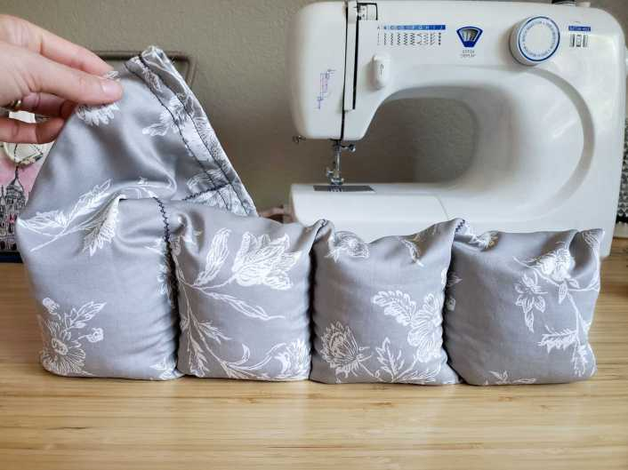The image shows the rice heat pad standing upright on its bottom end. A hand is holding up the top of the fabric to show how much space is left between the packed rice and the top of the pad. A sewing machine in in the background along with the sewing kit.