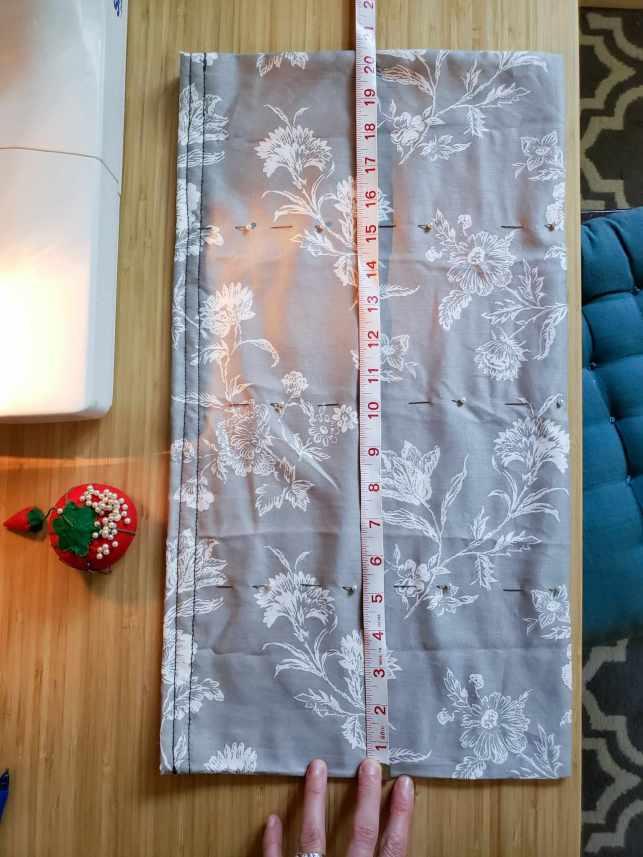An image of the pillow case laid out on the table vertically, there is the fabric tape measurer laid along its middle spanning twenty inches. There are four sewing pins placed horizontally across the pillow case in three places, one at five inches, one at ten inches, and one at fifteen inches.