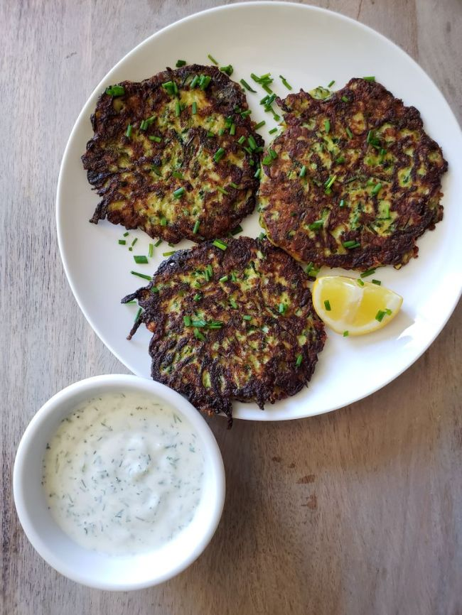 Three cooked zucchini fritters are now plated on a white ceramic plate, chopped chives and a wedge of lemon garnish the plate. There is a ramekin of yogurt dill sauce next to the fritters. The fritters are golden brown with hints of green and yellow showing through the mostly golden brown exterior.