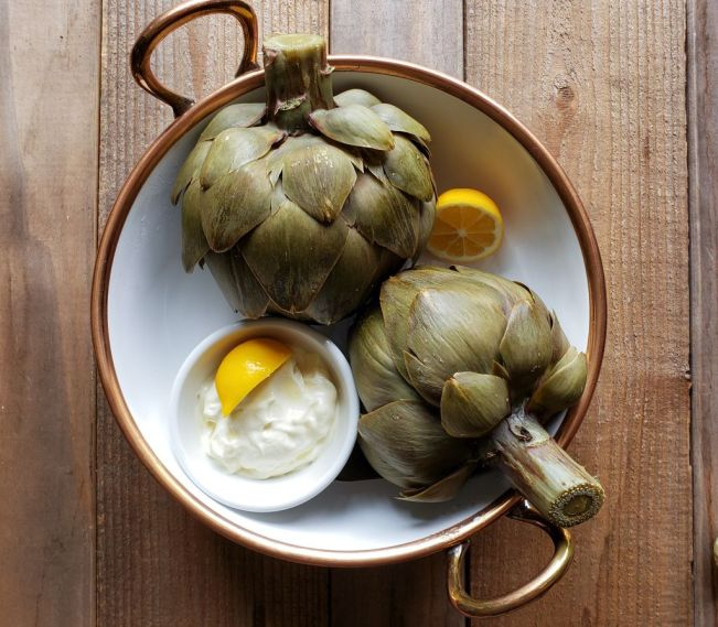 The two cooked artichokes sit in a white ceramic serving bowl that has a copper rim and handles. The artichokes are facing each other, pointed inwards being flanked by a half of lemon and a ramekin of mayonaise with a lemon wedge on top. The artichokes have now turned to a much darker green color compared when they were fresh.