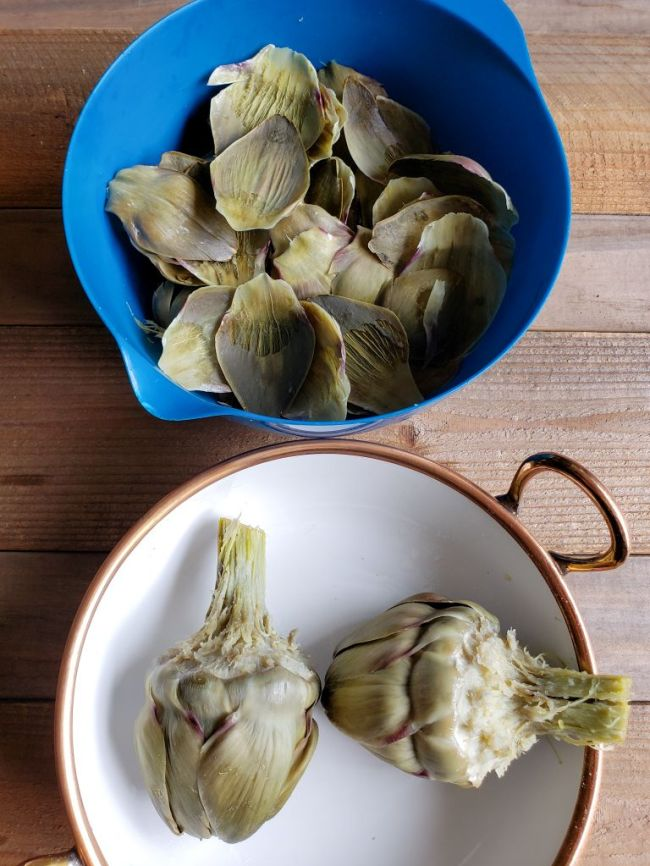 The image shows a blue mixing bowl on top full of discarded or eaten artichoke leaves. On the bottom is a white ceramic bowl that has two half eaten artichokes inside. The flesh is much lighter in color compared to the outer leaves.