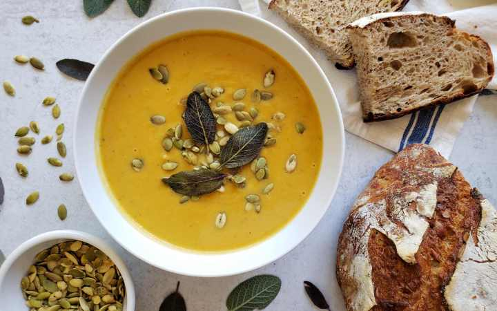 a bowl of butternut squash soup with sliced bread, pumpkin seeds, and sage leaves scattered around it