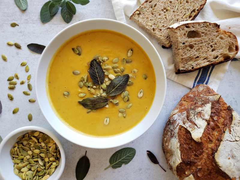 A bowl of butternut squash soup with sliced bread, pumpkin seeds, and sage leaves scattered around it with three fried sage leaves garnishing the center of the bowl of soup.