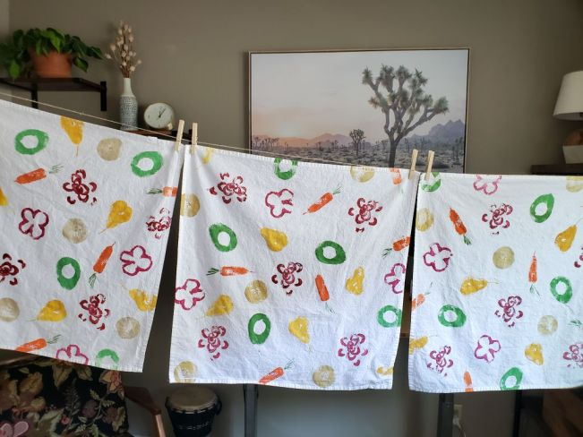 Three completed fruit and veggie stamped tea towels are air drying, hanging from a line with clothespins. They are drying inside of a house with a small chair in the corner, next to a hand drum and an image of a desert scene hanging on the wall in the background. There is also a clock, plant, and lamp off towards the corners of the image.