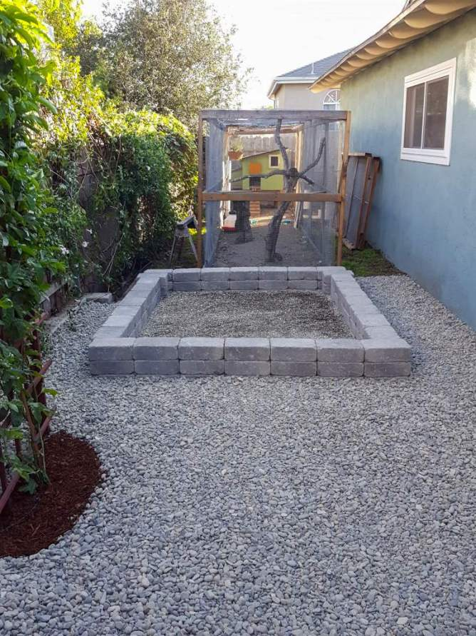 A concrete paver foundation is shown, it sits almost a foot above the ground and is surrounded by gravel. A greenhouse frame will soon be constructed using this as the base. A chicken coop and run are visible  in the background, making good space of the long, yet slightly narrow side yard.