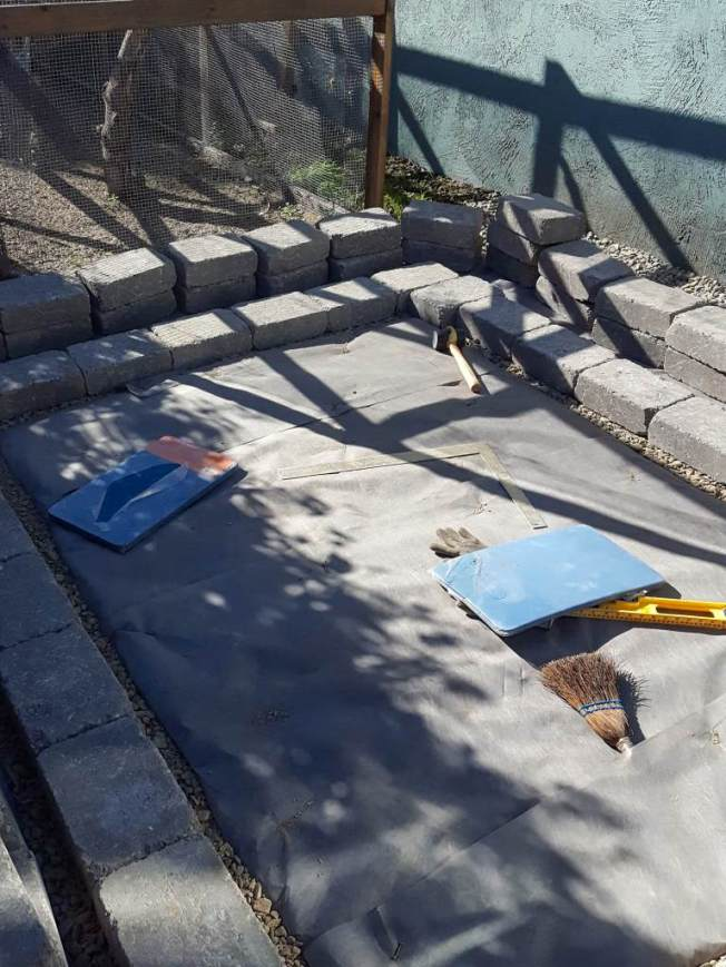 The foundation is being laid with concrete pavers. The first layer of blocks has been laid while the other pavers are sitting nearby when it is time to attach them on top of the first layer. A rubber mallet, level, and right angle measuring tool are visible.