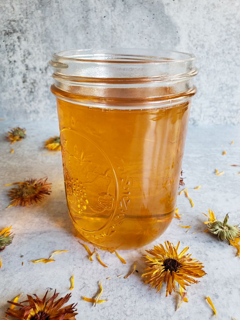 The finished calendula oil is shown in a pint mason jar. The oil is a beautiful golden honey color after it has been infused with the dried calendula flowers and steeped for almost a month. There are various dried calendula flowers scattered about around the jar.