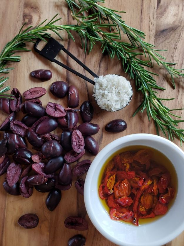A birds eye view of a wooden cutting board with rosemary sprigs, a heaping tablespoon of celtic grey salt, kalamata olives sliced in halves, and a white ramekin of of sun-dried tomatoes submerged in olive oil.