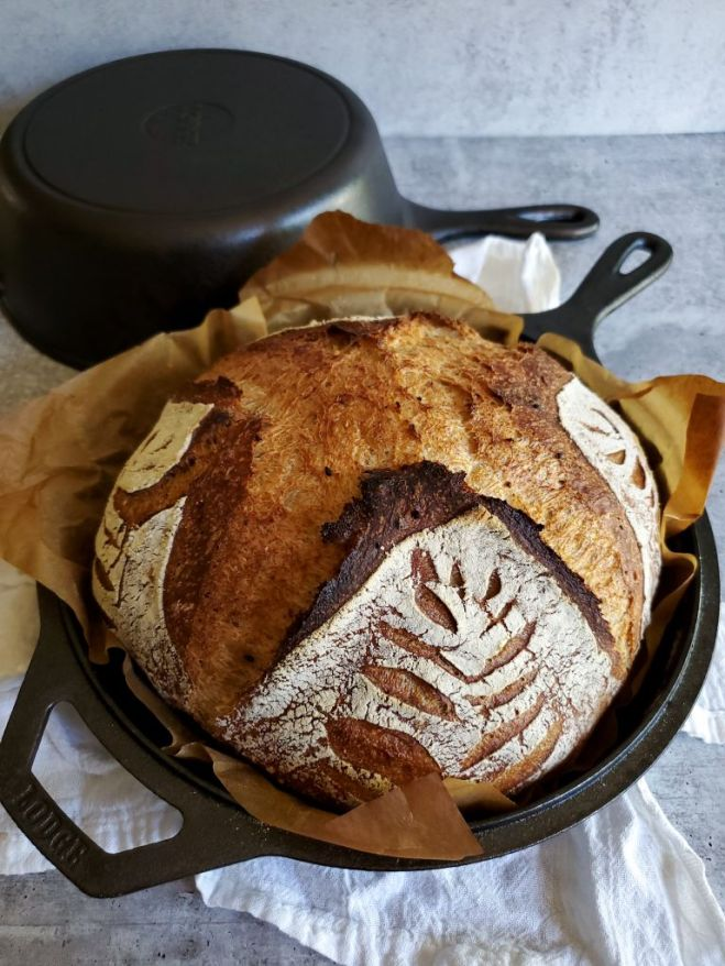 A loaf of freshly baked sourdough bread is shown still in its cast iron baking pan. The bread is light brown to darker brown in the more crispy parts. The strands of gluten are visible on the crust of the bread.