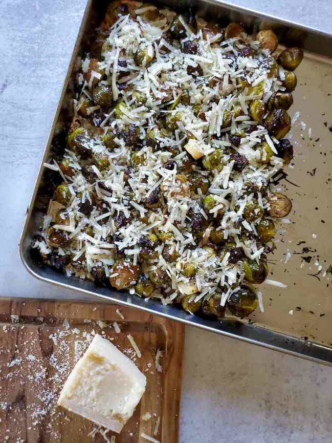 The roasted brussels sprouts have been pushed to one side of the baking sheet and they have been topped with freshly grated parmesan cheese. A wood cutting board with a partial block of parmesan cheese is shown next to the baking sheet.