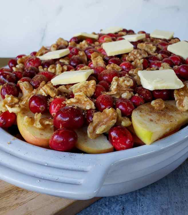 An image taken at an angle after the dish has been completed with two layers of all of the toppings. The apples, walnuts, and cranberries are towering over the edges of the dish but it will cook down once baked.